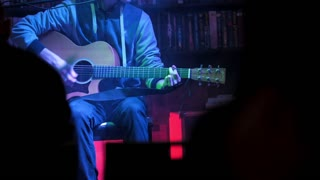 Guitarist plays acoustic guitar in night club, close up