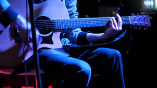 Guitarist plays concert acoustic guitar in night club
