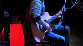 Guitarist - young man - plays concert acoustic guitar in night club