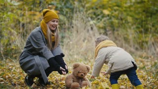 Happy family concept - little daughter with her mommy and Taddy bear plays with yellow leaves in autumn park