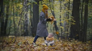 Happy family concept - little daughter with her mother plays with yellow leaves in autumn forest, slow-motion