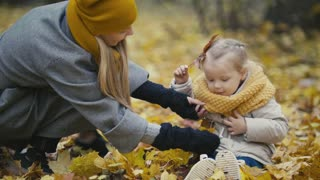 Happy family concept - little daughter with her mother plays with yellow leaves in autumn park