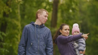 Happy family: Father, Mother and child - little girl in autumn park: mammy shows to baby something