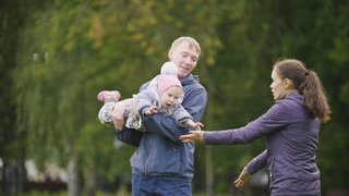 Happy family: Father, Mother and child - little girl walking in autumn park: a woman hugs a man and a child, slow motion