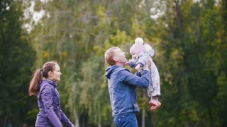 Happy family: Father, Mother and child - little girl walking in autumn park: dad throws the baby in her arms, slow motion