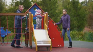 Happy family: Father, Mother and child - little girl walking in autumn park: mamy, dad and baby playing at playground