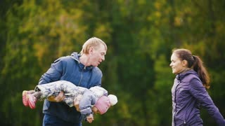 Happy family: Father, Mother and child - little girl walking in autumn park: playing at the grass, slow motion