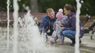 Happy Family - mother, Father and baby daughter near fountains in the city park - girl looking to water