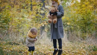 Healthy family concept - little blonde girl with her mommy spend time in autumn park - jumping and have fun