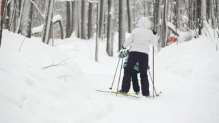 Healthy sport family - mammy and child - skiers in winter snow forest