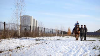 Hippotherapy for kid with cerebral palsy syndrome at winter cold day - contact kids therapy and rehabilitation horse-riding club - front view