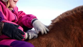 Hippotherapy for kid with cerebral palsy syndrome at winter cold day - contact kids therapy and rehabilitation horse-riding club - young girl and her mother rides on horse, pats horseback, close up