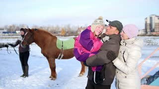 Hippotherapy for kid with cerebral palsy syndrome at winter cold day - contact kids therapy and rehabilitation horse-riding club - young girl, her mother and father near horse