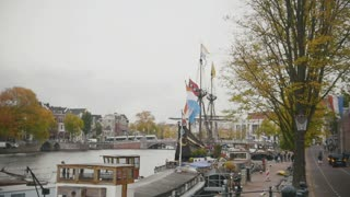 Historically authentic frigate moored on the canal in Amsterdam, Holland, Netherlands, slow-motion