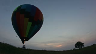 Hot air balloon takes off at sunset