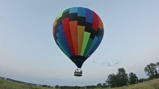 Hot air balloon takes off in meadow