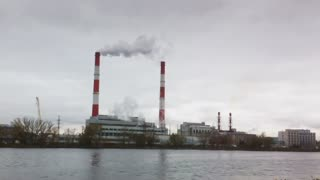 Industrial landscape - thermal power plant over the river, smoke from tube