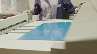 industrial printing process - worker monitors the printing process, close up