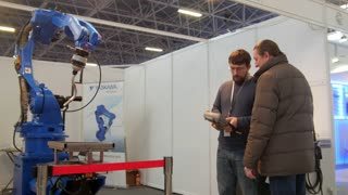 KAZAN, RUSSIA, 9 DECEMBER 2016, 15th International Specialised Exhibition. Mechanical Engineering. Metalworking. 10th International Exhibition. Technowelding. two man looking on robo arm for welding