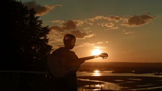 Landscape at sunset with kid and music: boy having fun and play guitar, silhouette
