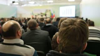 Lecturer tells and shows presentation on screen for listeners at agricultural seminar