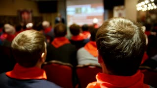 Listeners in red ties listens for lecturer who tells and shows presentation on screen