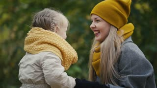 Little blonde girl with her mommy spend time in autumn park - play and clap hands, close up