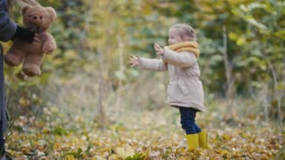 Little blonde girl with her mommy spend time in autumn park - plays with teddy bear