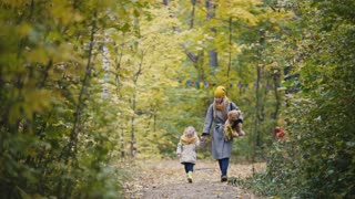 Little blonde girl with her mommy walks in autumn park alley, sportsmen runs at background
