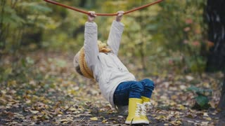 Little girl in yellow boots plays with rope at playground on autumn park