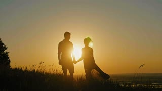 loving couple - brave young man and beautiful girl at sunset silhouette