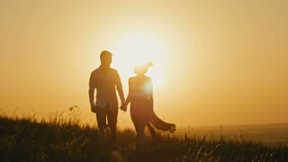 loving couple - brave young man and beautiful girl at sunset silhouette,