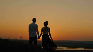 loving couple - brave young man and beautiful girl stands on high hill and looking to sunset silhouette, slider shot