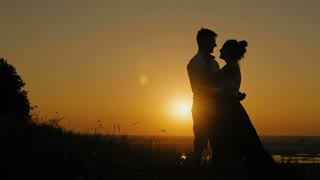 loving couple - brave young man and beautiful girl stands on high hill at sunset and have hugs and kiss, silhouette, slider shot