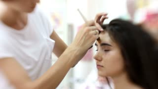 Makeup artist in beauty salon makes for attractive girl beautiful makeup, hairdresser makes hairstyle, the beginning of the process, close up