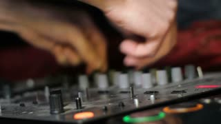 Male DJ Controls sound remote in night club