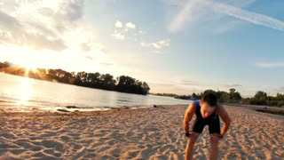 Male runner at the beach takes a break to get his breath back, slow motion