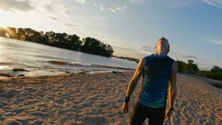 Male runner at the beach takes a break to get his breath back