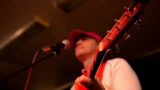 Man in red cap in the garage playing guitar and sing in microphone