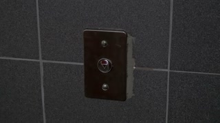 Man presses a button in an elevator