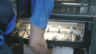 Man using industrial control panel of the Printing machine.