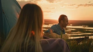 Man with friends plays acoustic guitar and sings in camping outdoors on high hill at summer sunset