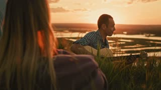 Man with friends plays acoustic guitar in camping outdoors on high hill at summer sunset