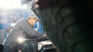Mechanic in car service - repairing in engine compartment for luxury SUV - slider shot