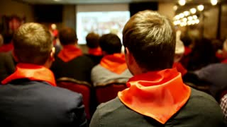 Meeting of the Communist pioneers Komsomol - listeners in red ties listens for lecturer who tells and shows presentation on screen