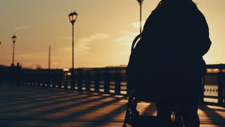 mom with baby stroller in spring sunset silhouette