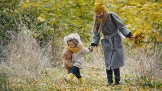 Mother and her daughter little girl playing in a autumn park - mom gives child holding a herbarium and kicking yellow leaves