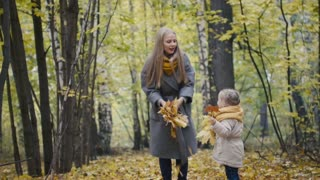 Mother and her daughter little girl playing in a autumn park - mommy and child throw leaves
