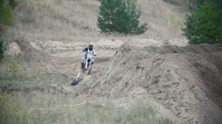 Motocross racer biker in blue jumpsuit jumping on track in rapid shoot, slow motion, close up