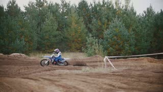 Motocross racer mxgirl on dirt bike jumping on track among rhe spruces in rapid shoot, Slow motion, close up